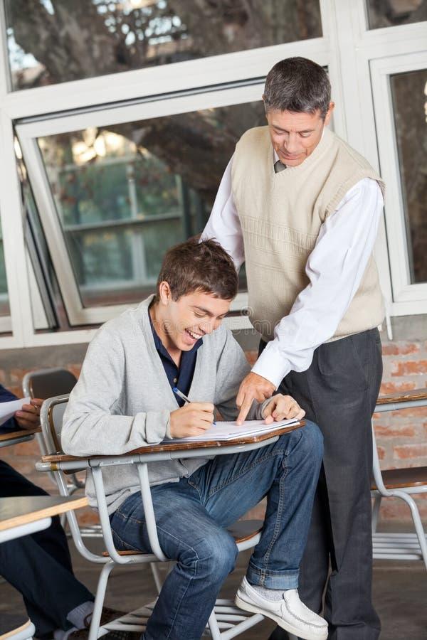 微笑的学生,当解释测试的老师时 免版税库存照片