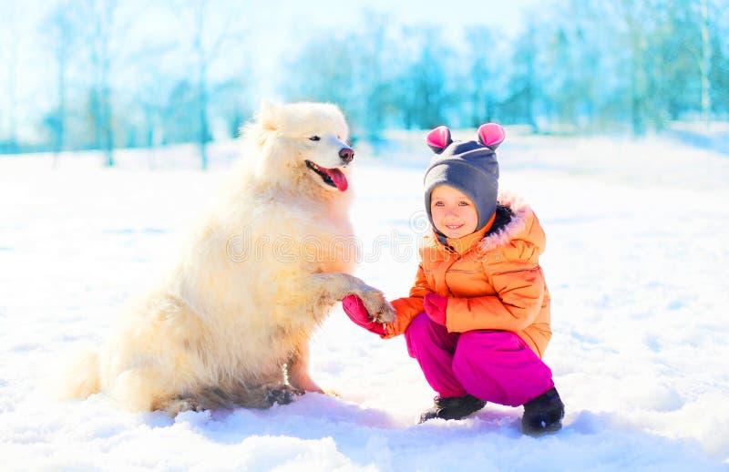 微笑的孩子和白色萨莫耶特人在雪冬天尾随使用 免版税库存照片