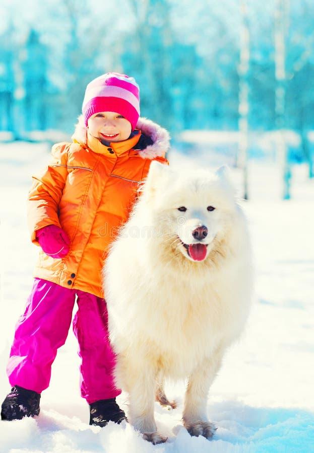 微笑的孩子和白色萨莫耶特人在雪冬日尾随使用 库存照片