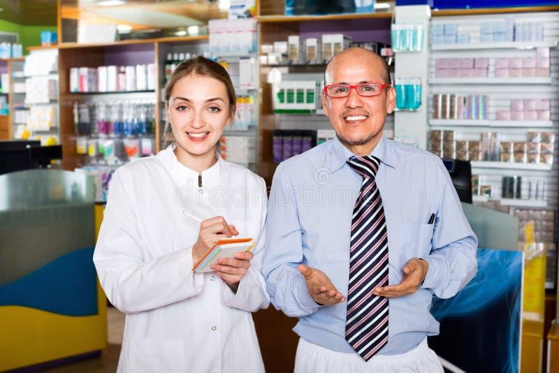 微笑的宜人的药剂师和药房技术员 免版税库存照片