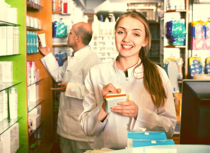 微笑的宜人的药剂师和药房技术员 免版税库存图片