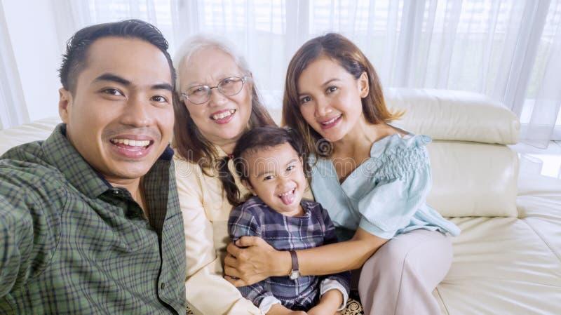 微笑的家庭在家拍团体照片 免版税图库摄影
