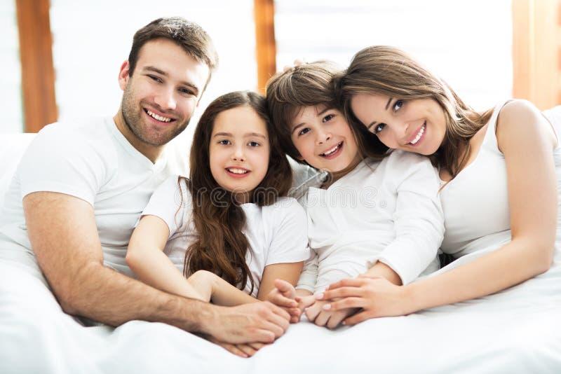 微笑的家庭在床上 库存照片
