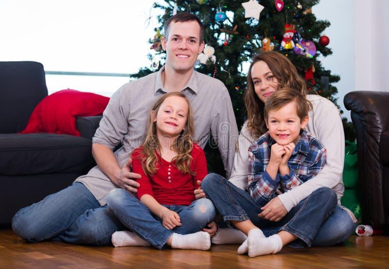 微笑的家庭成员为与圣诞树的照片做准备 免版税库存图片