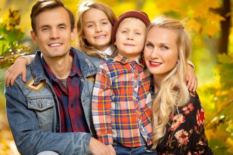 微笑的家庭画象有孩子的步行的在秋天公园 图库摄影