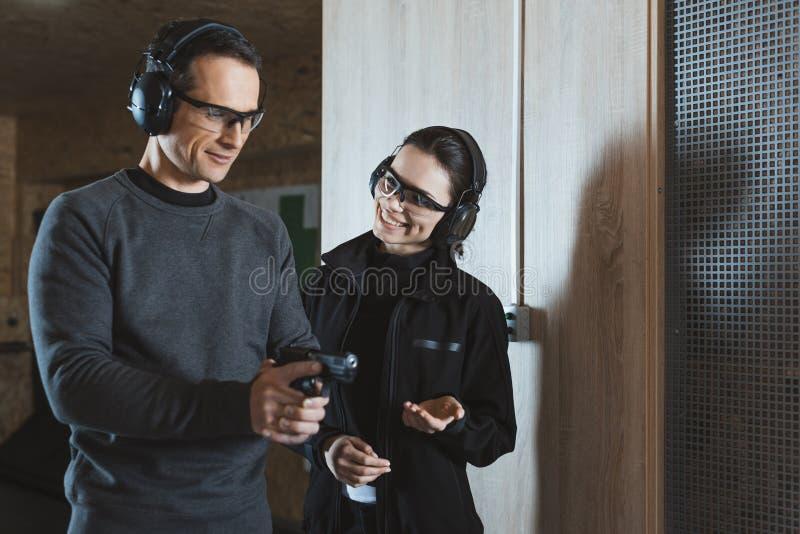 微笑的射击辅导员谈话与客户 库存照片