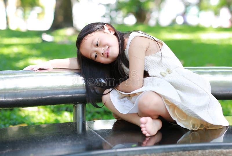 微笑的小亚裔儿童女孩画象在晴朗的绿色公园 免版税库存图片