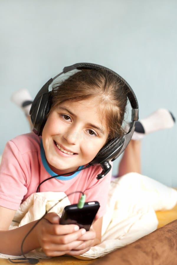 微笑的小女孩享受音乐 库存照片