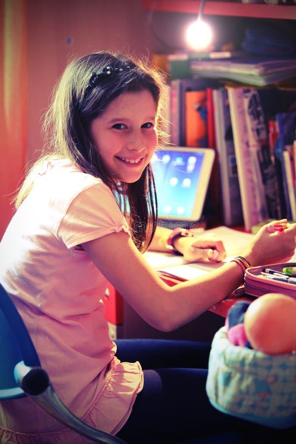 微笑的小女孩在有移动式摄影车和片剂的卧室 库存图片