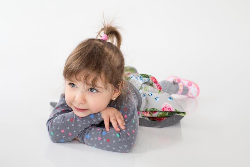 微笑的小女孩在白色背景的地板上说谎 库存照片