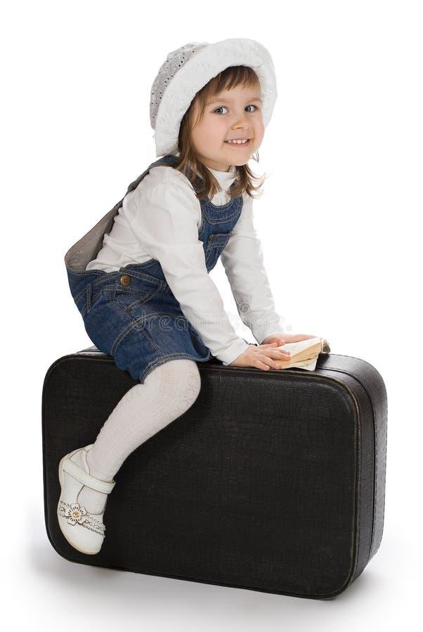 微笑的小女孩坐手提箱 库存图片