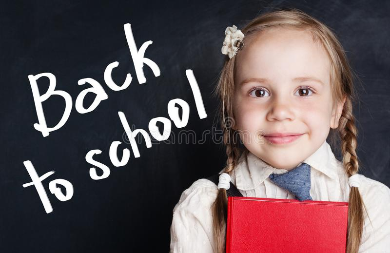 微笑的小女孩学生 回到横幅学校 图库摄影