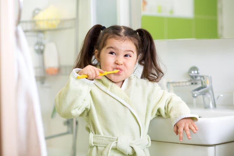 微笑的小女孩掠过的牙在卫生间里 库存照片