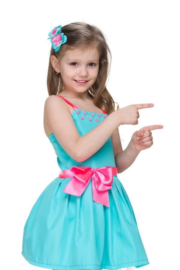 微笑的小女孩显示她手指对边 免版税库存图片