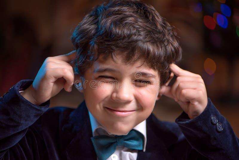微笑的小孩塞住他的耳朵和结束他的眼睛,但是 库存照片