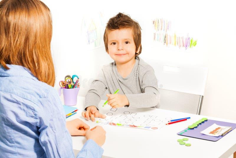 微笑的小男孩举行铅笔和积土形状 免版税库存图片