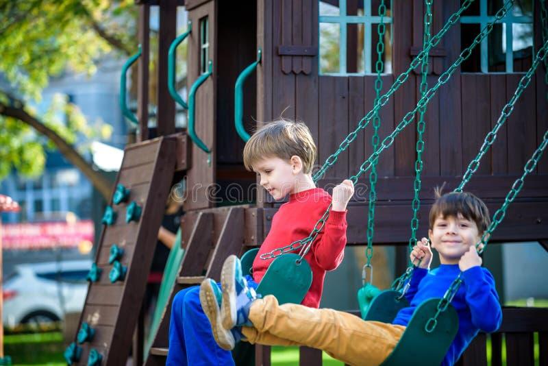 微笑的小男孩和他的兄弟朋友摇摆的 孩子p 免版税库存照片