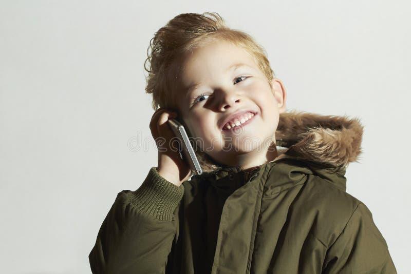 微笑的小男孩谈话在手机 冬天外套的愉快的孩子 方式孩子 孩子 库存图片