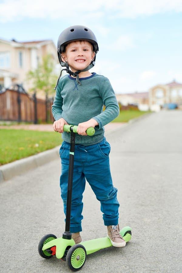 微笑的小男孩骑马滑行车 免版税库存图片