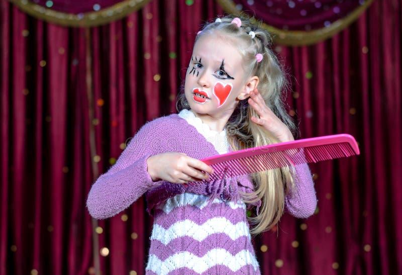 微笑的小白肤金发的女孩佩带的手势构成 图库摄影