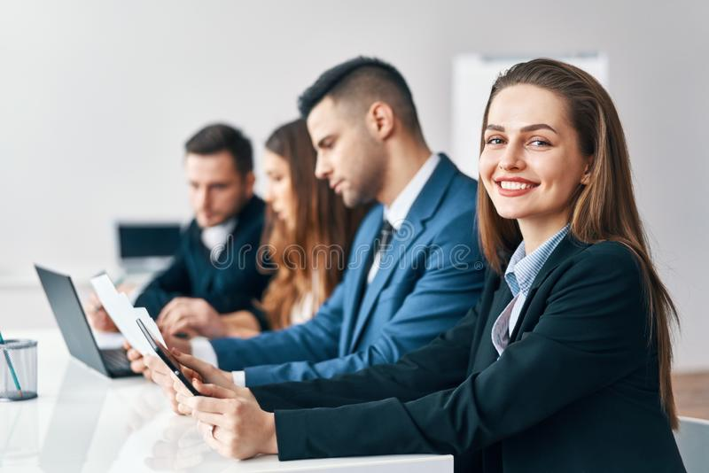 微笑的小组画象连续坐一起在桌上的商人在一个现代办公室 免版税库存照片