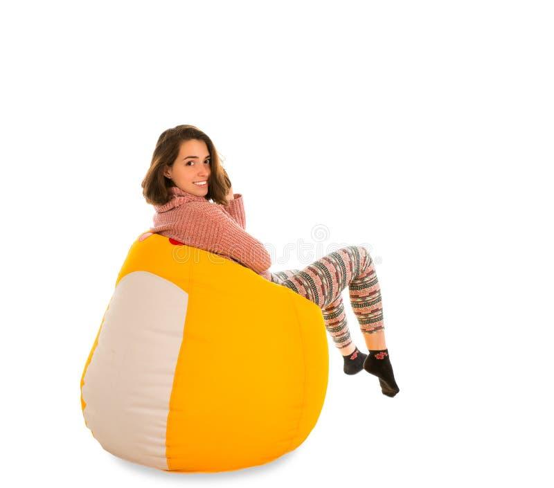 微笑的少妇侧视图坐黄色装豆子小布袋椅子 库存图片
