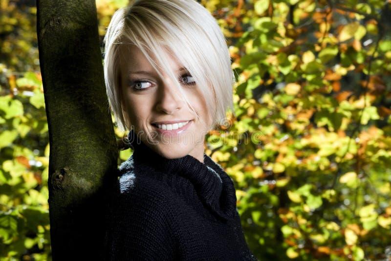 微笑的少妇在秋天森林地 免版税图库摄影