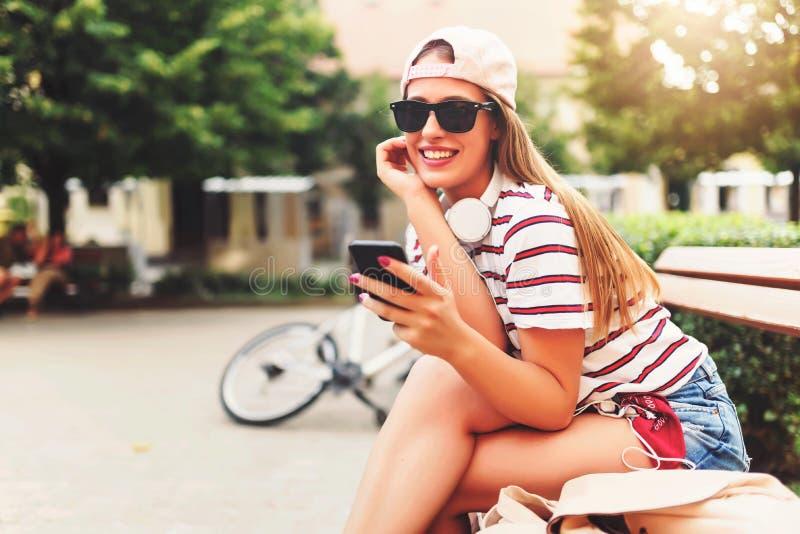 微笑的少妇坐一条长凳在夏天使用巧妙的电话 免版税图库摄影