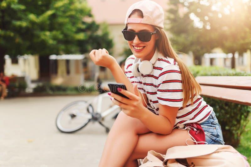 微笑的少妇坐一条长凳在夏天使用巧妙的电话 库存图片