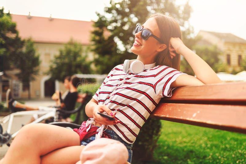 微笑的少妇坐一条长凳在夏天使用巧妙的电话 库存照片
