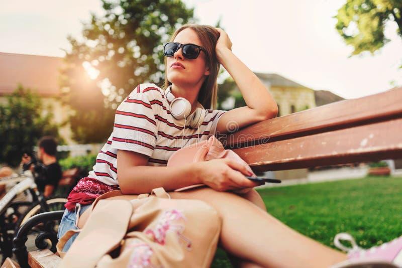 微笑的少妇坐一条长凳在夏天使用巧妙的电话 免版税库存照片