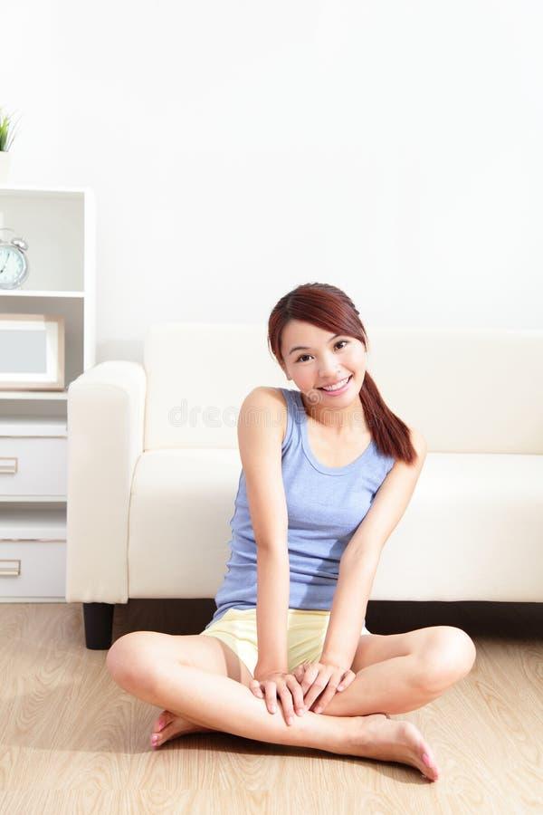 微笑的少妇坐地板 免版税库存图片