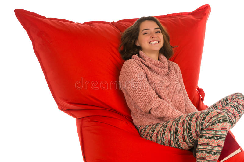 微笑的少妇坐居住的红色装豆子小布袋沙发椅子 图库摄影