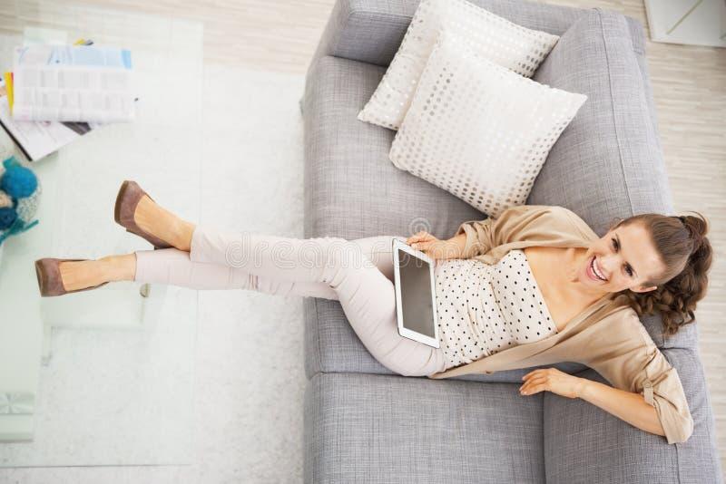 微笑的少妇坐有片剂个人计算机的沙发 免版税库存照片