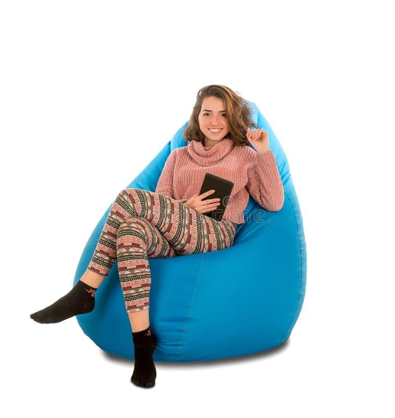 微笑的少妇坐蓝色装豆子小布袋主持和举行a 免版税图库摄影