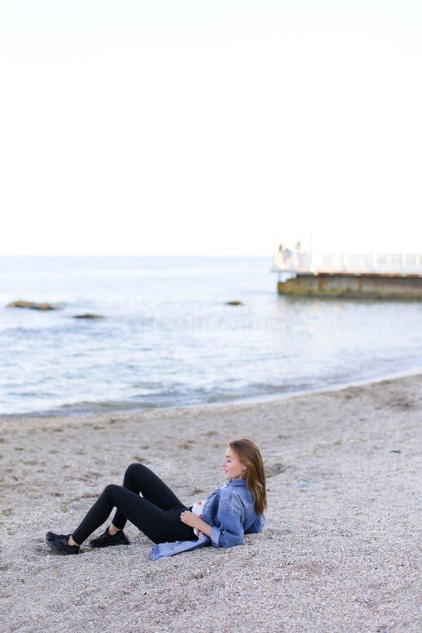 微笑的少妇基于海滩并且摆在秘密审议,坐 库存照片