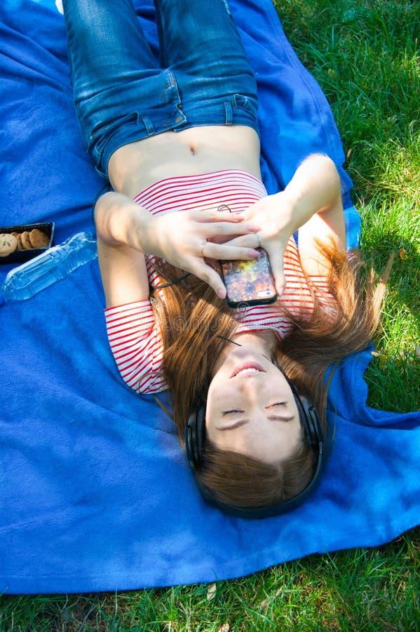 微笑的少妇感人的手机和说谎在草 免版税库存图片
