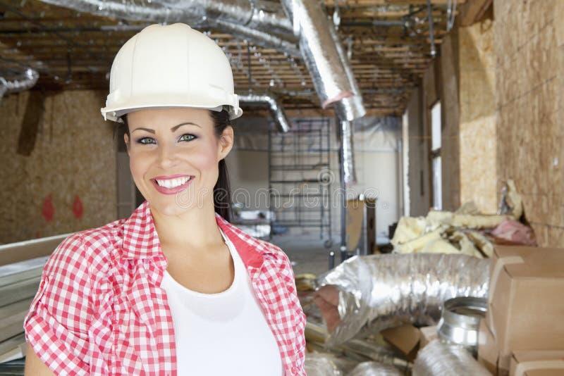 微笑的少妇承包商特写镜头画象建造场所的 免版税库存照片