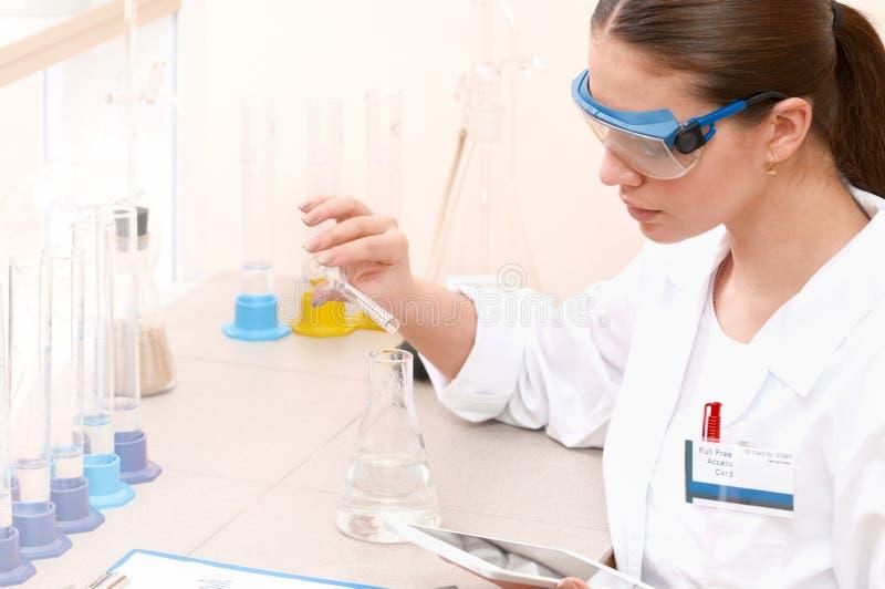 微笑的少妇科学家顶视图,当工作在实验室里时 免版税库存照片
