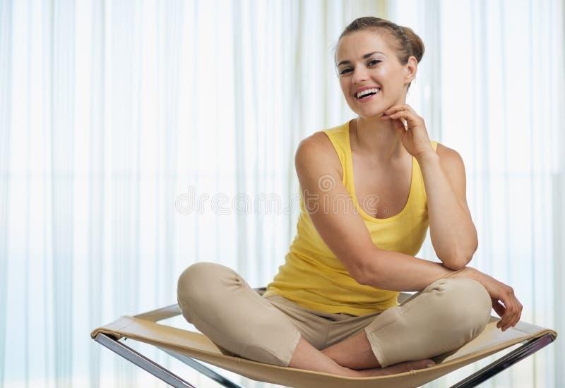 微笑的少妇纵向坐椅子 免版税库存照片