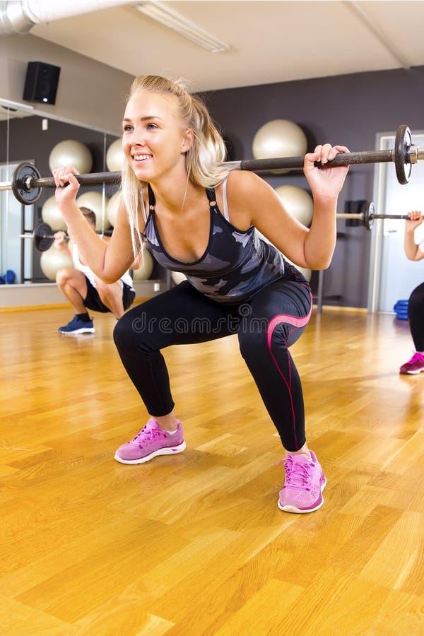 微笑的少妇训练蹲在小组的锻炼在健身健身房 库存照片