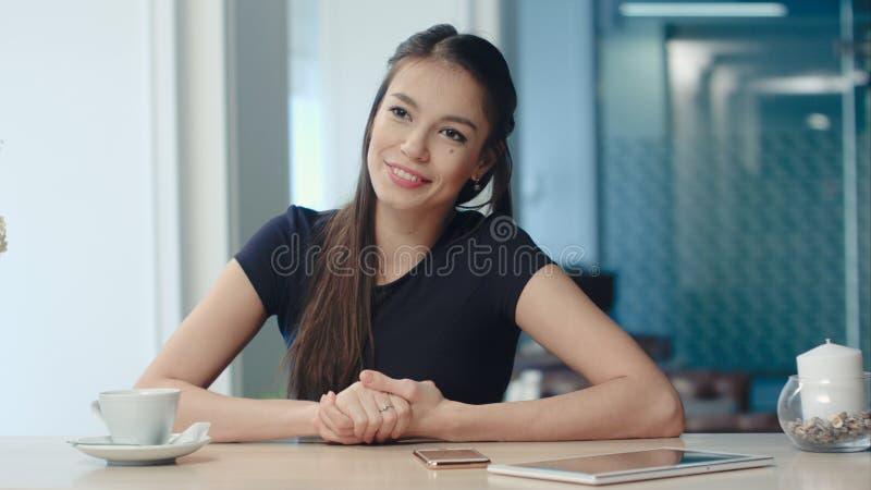 微笑的少妇讲故事对一个朋友在咖啡馆 免版税库存照片