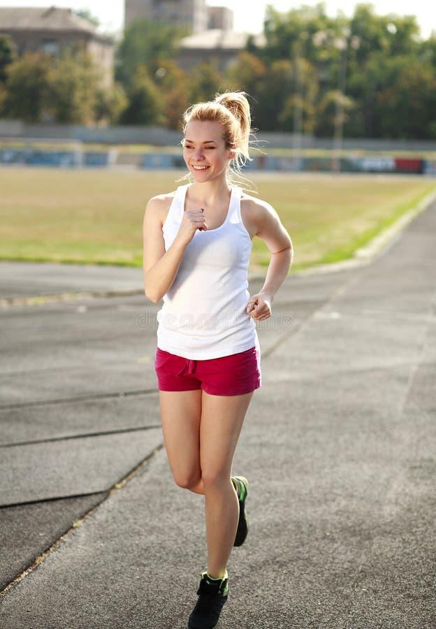 微笑的少妇跑步,训练户外 库存照片