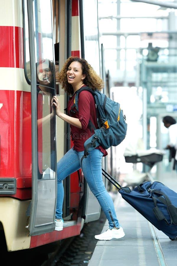 微笑的少妇输入的火车 免版税图库摄影