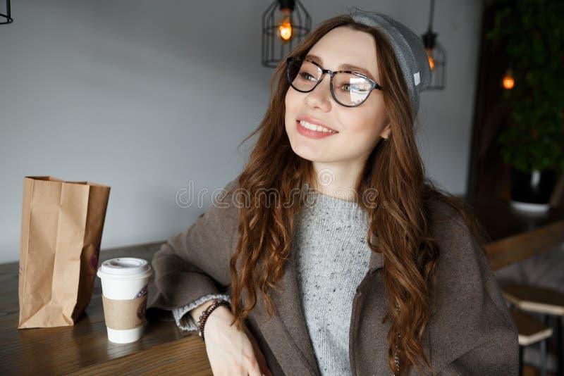 微笑的少妇饮用的咖啡画象在咖啡馆的 图库摄影