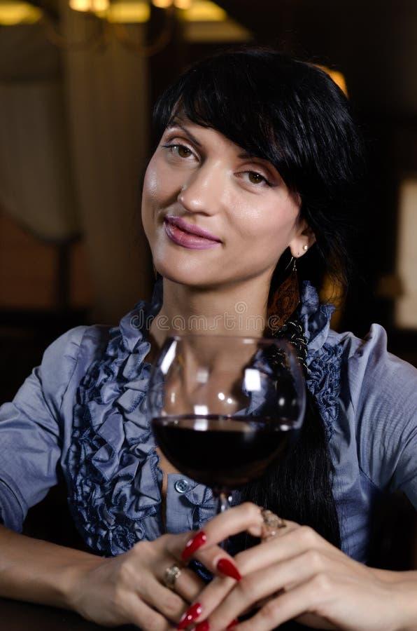 微笑的少妇,当喝红葡萄酒时 免版税库存照片