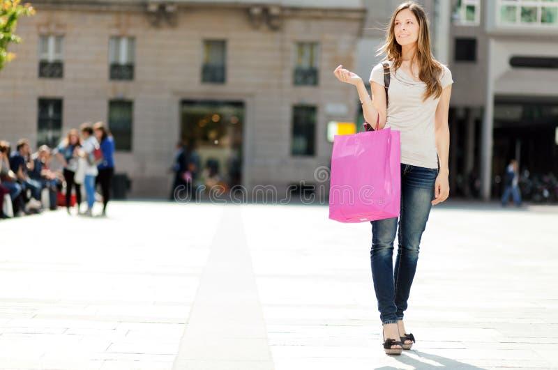 微笑的少妇购物在城市 库存图片