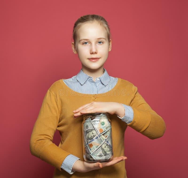 微笑的少年和金钱获利在珊瑚桃红色背景的瓶子 免版税图库摄影