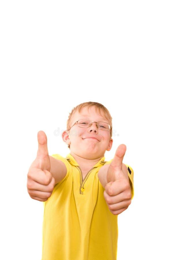 微笑的少年显示在二个现有量的赞许符号 免版税库存照片
