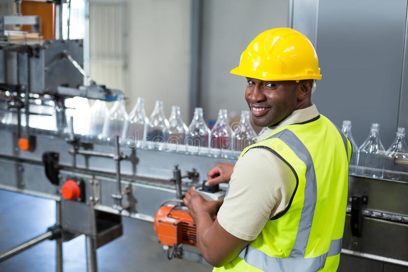 微笑的工厂劳工运行的机器在工厂 免版税库存照片